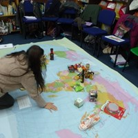 International and global citizenship Woman organising an activity on a large map of the world on the floor