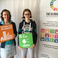 "Global Goals 2017 - 4 Woman and girl holding up signs which read ""Sustainable cities and communities"" and ""Life on land"""