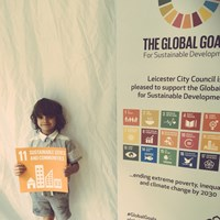 "Global Goals 2017 - 5 Young boy holding up a sign which reads ""Sustainable cities and communities"""