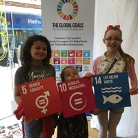 "Global Goals 2017 - 9 Three girls holding up signs, ""Gender equality"", ""Reduced inequalities"", ""Life below water"""