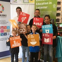 Global Goals 2017 - 10 Group of adults and children all holding up various coloured signs