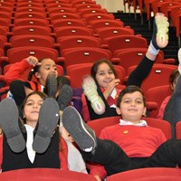 English Martyrs 17 Children from English Martyrs School sitting in an auditorium with their feet up